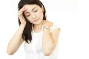 肩こりと頭痛に悩む女性